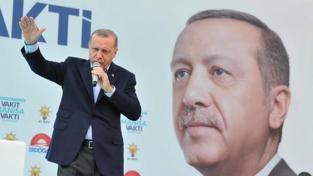 Erdogan sprichtin ein Mikrofon, hinter ihm ein rieisiges Porträt seiner selbst.