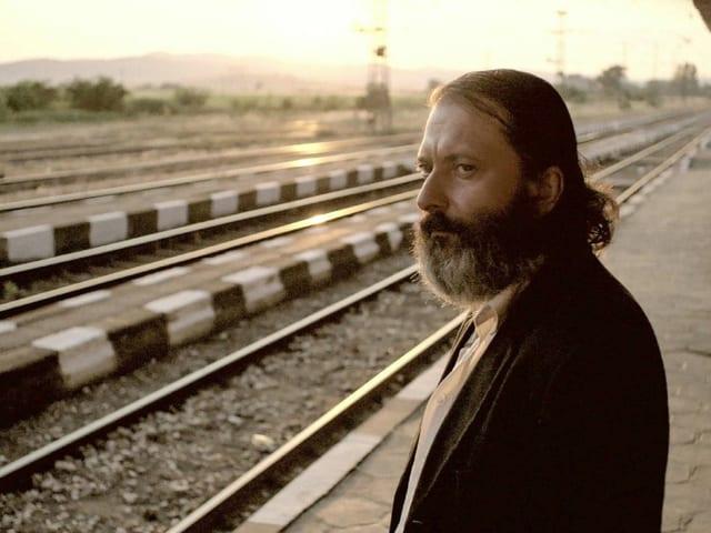 Ein Mann steht am Bahnhof und blickt auf ein Gleis. Hinter ihm scheint die Abendsonne.