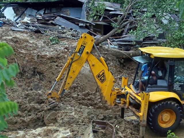 Ein Bagger gräbt im Erdrutschgebiet in Sri Lanka. Dahinter ein zerstörtes Haus.