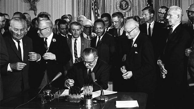 Johnson unterschreibt an einem Schreibtisch ein Dokument. Hinter ihm stehen etwa vierzig Männer in Anzügen. Direkt hinter Johnson steht Martin Luther King.