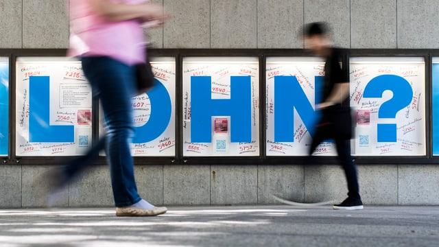 """Zwei Passanten spazieren vor einem Plakat mit einer blauen Aufschrift """"Lohn"""" vorbei."""