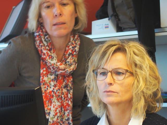 Zwei Frauen schauen in einen Computerbildschirm.