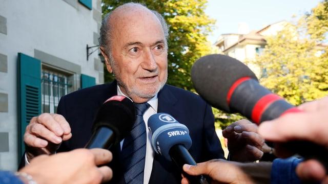 Blatter spricht in ihm entgegengehaltene Medien-Mikrofone.