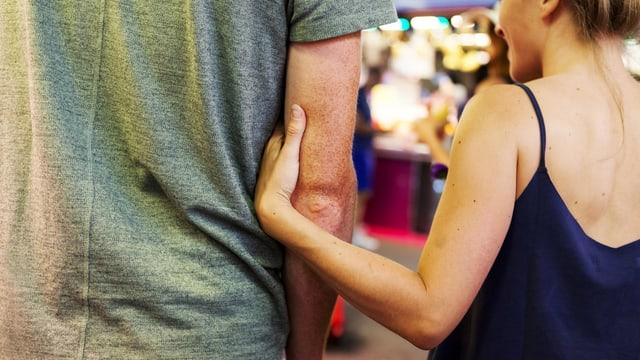 Eine Frau hält einen Mann am Arm.