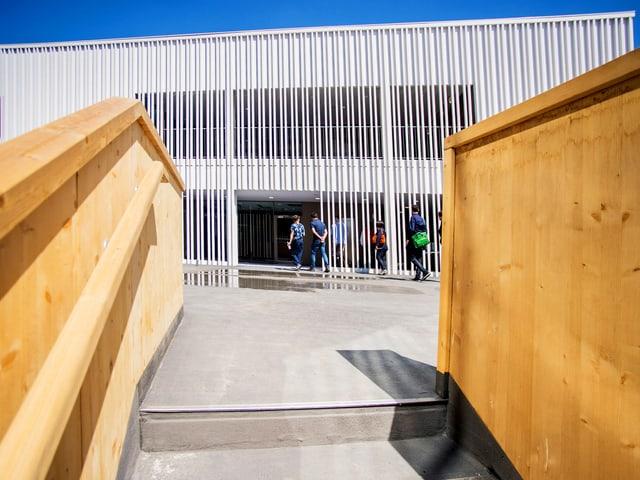 Eine Treppe mit einem Geländer aus Holz. Hinten ist ein weisses Gebäude.