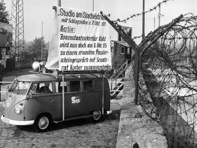 Bus mit Lautsprechern auf dem Dach steht neben Berliner Mauer