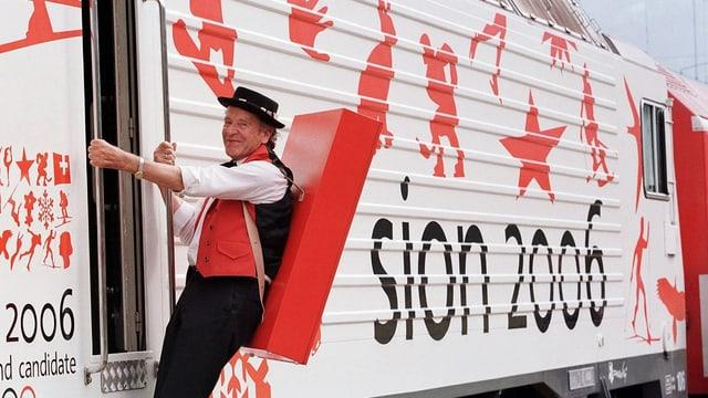 "Mann in traditioneller Kleidung hängt an Zugeingang, Zug mit Aufschrift ""Sion 2006"""