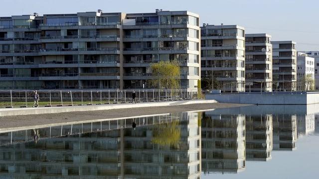 Vier Wohnblöcke in grau, davor ein See, in dem sich die Häuser spiegeln.