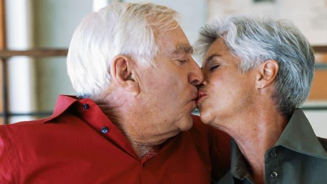 Ein älteres Paar küsst sich.
