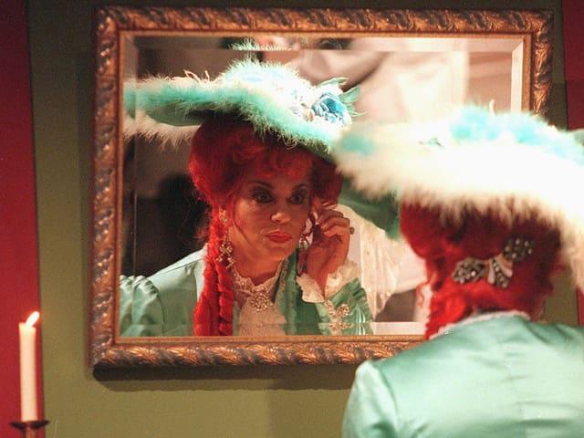 Eine Schauspielerin betrachtet sich im Spiegel.