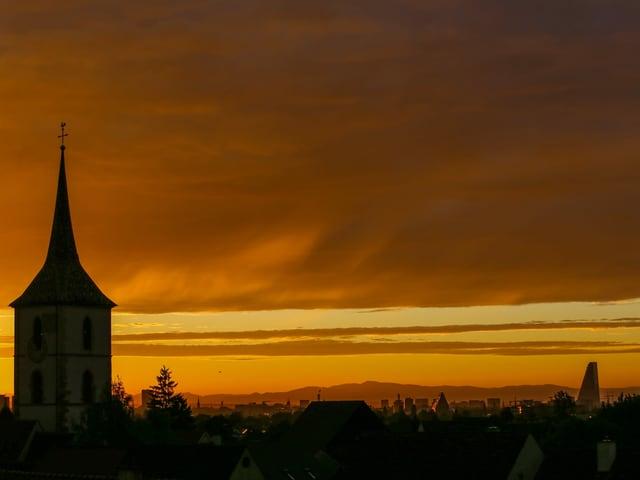 Blick auf eine Kirche mit gelb-orangen Himmel im Hintergrund.