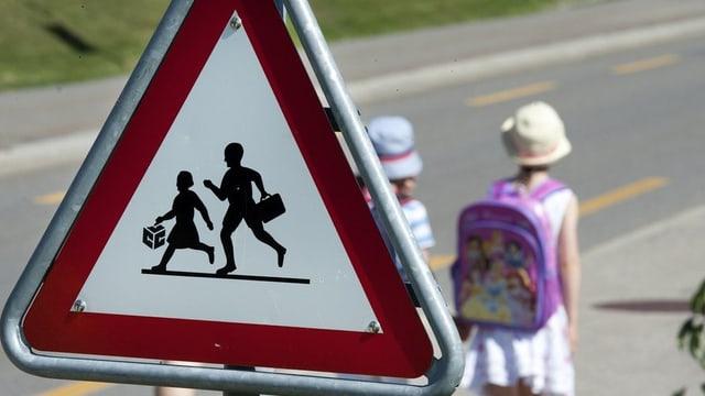 Schulweg-Schild mit Schülern im Hintergrund.