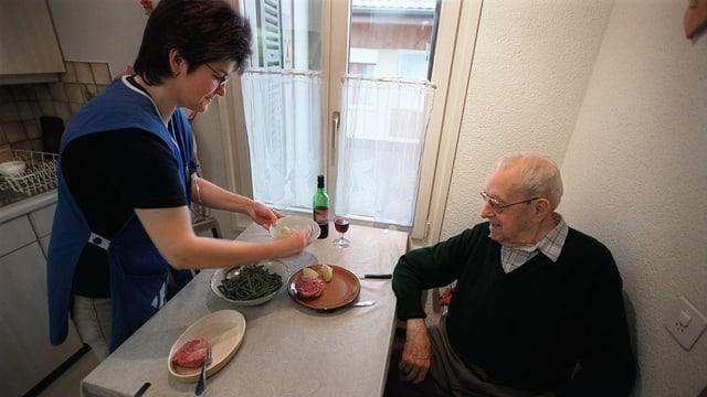 Eine Pflegerin serviert einem älteren Mann das Essen.