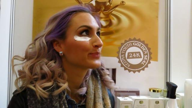 Eine Frau mit Crème unter den Augen.
