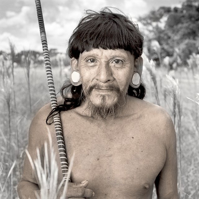 Ein Mann mit nackten Oberkörper und auffälligem Ohrschmuck.