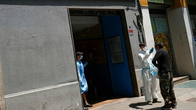 Einem Mann in Barcelona wird die Temperatur gemessen.