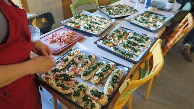 Belegte Brote, die überbacken werden, liegen auf fünf Blechen bereit.