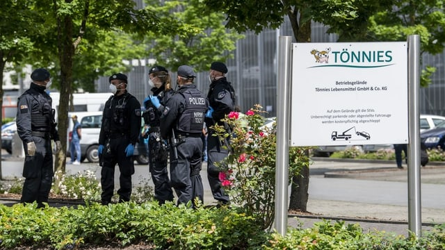 Polizisten in Schutzkleidung vor dem Fabrikgelände.