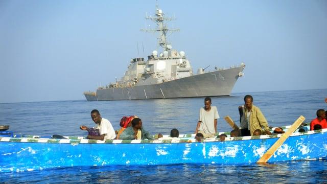 Männer und Frauen auf einem kleinen blauen Bott, dahinter ein Kriegsschiff der US-Navy.