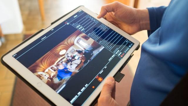 Ein Mann hält in seinen Händen ein Tablet, auf dem fotografische Informationen sichtbar sind.