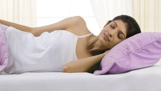 Eine Frau schläft auf der Seite liegend.