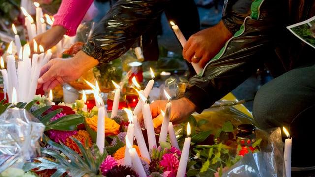 Jugendliche zünden Kerzen an an einem Gedenkmarsch für das Opfer der Messerstecherei vor dem Kaufleuten.