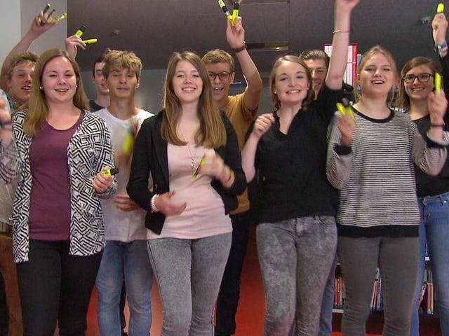 Eine Schulklasse hält gelbe Marker in die Kamera.
