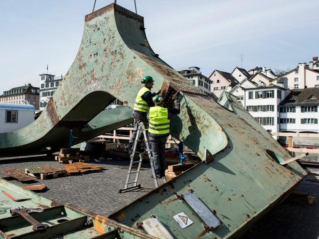 Arbeiter werkeln an einem Teil des Fusses des Zürcher Hafenkrans.