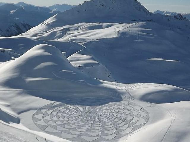 Schneelandschaft in den Bergen mit in den Schnee gestampften Mustern, die an Sterne erinnern.