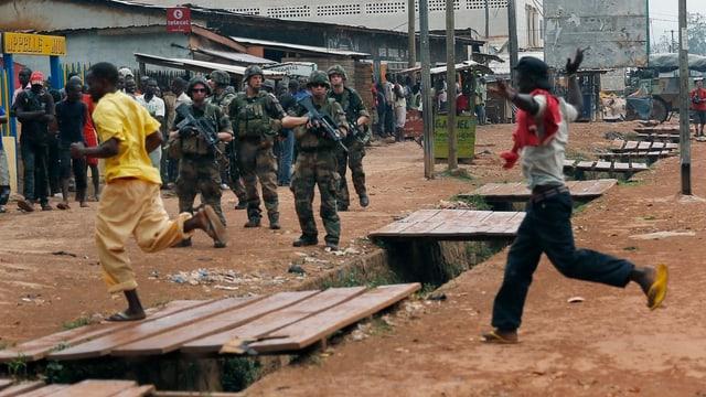Zwei Menschen rennen über eine Holzbrücke, dahinter bewaffnete Soldaten.
