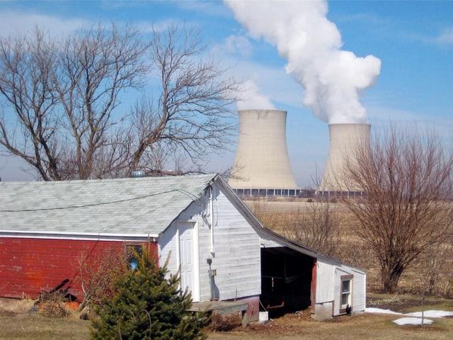 Im Hintergrund zwei Kühltürme vor blauem Himmel. Im Vordergrund ein rotes Farmhaus mit Bäumen umgeben