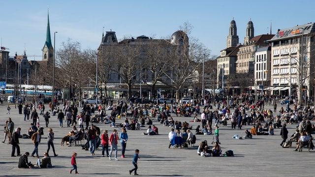Sechseläutenplatz in Zürich; viele Leute sitzen auf dem Boden und geniessen die Sonne.
