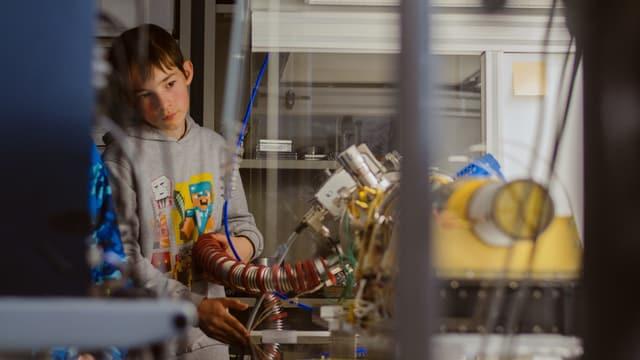 Ein Kind schaut sich ein wissenschaftliches Instrument an.