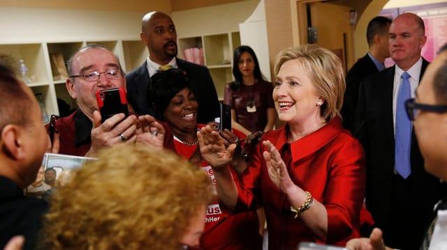 Hillary Clinton cun in deux pieces cotschen e fatscha rienta. Ella tegn ils mauns sin altezia da la schugliala. Ella è circumdada da fans e reporters.