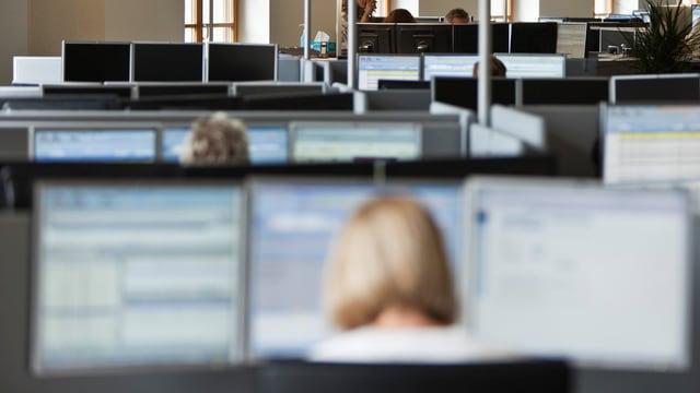 Ein Call-Center mit zwei Mitarbeitern und einigen unbesetzten Arbeitsplätzen.