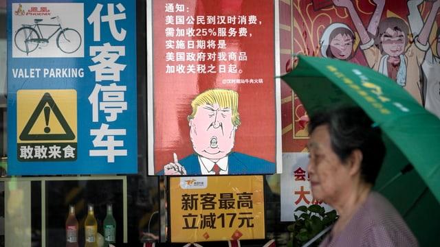 Eine Frau geht an einem Plakat vorbei, das eine Karikatur von Donald Trump zeigt.