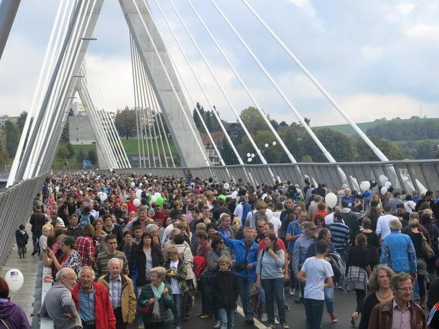 Tausende wandern über die neue Freiburger Poya-Brücke.