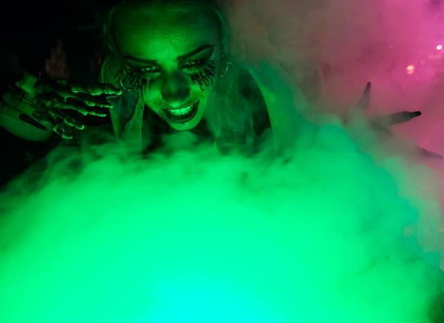 Eine Person, verlkeidet als Hexe über einem grünen Nebel.