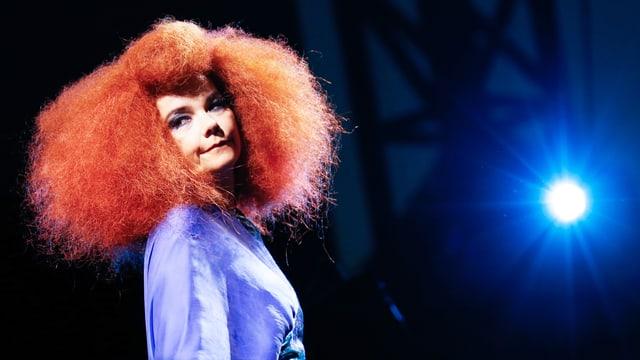 Die Sängerin Björk auf der Bühne mit roten Haaren und blauem Kleid.