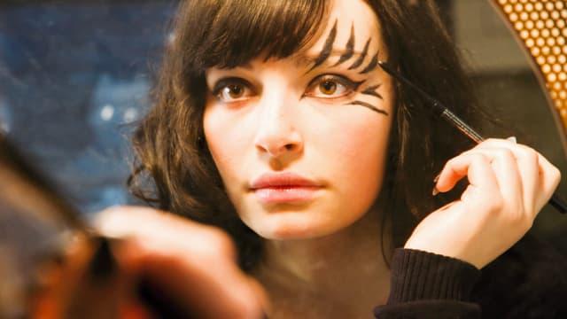 Eine junge Frau schminkt sich vor einem Spiegel.