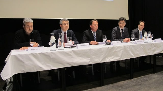Fünf Leute sitzen an einem Tisch