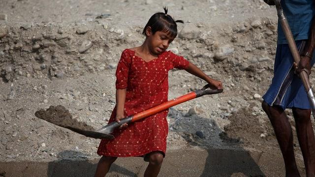Ein achtjähriges Mädchen schaufelt in Indien Steine.