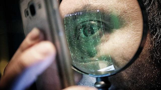 Ein Mann schaut durch eine Lupe auf sein Smartphone. Auf dem Glas spiegelt sich Computercode.
