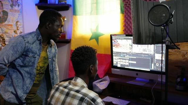 Zwei schwarze Männer vor einem Computer.