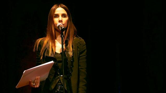 Eine Frau mit langen Haaren steht vor einem Mikrofon.