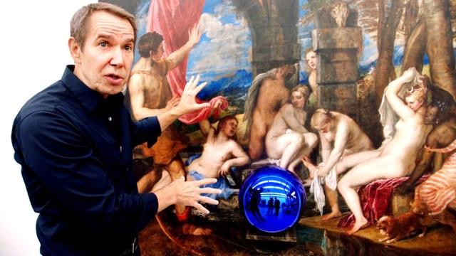 Jeff Koons steht vor einem Gemälde. Er gestikuliert.