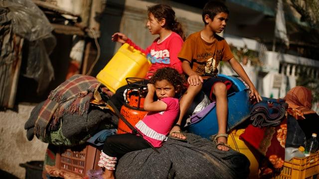 Drei Kinder sitzen auf einem vollbepackten Wagen.