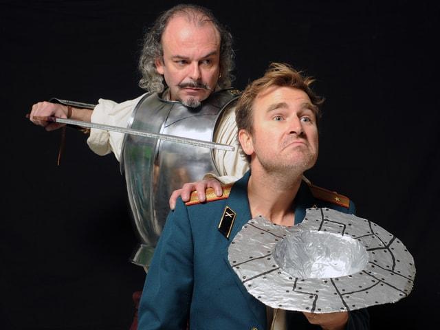 Ein Ritter bedroht von hinten einen Mann mit einem Schwert.