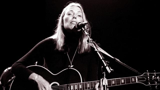Eine blonde Frau mit Gitarre singt.