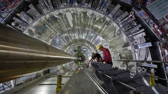 Zwei Männer reparieren den Teilchenbeschleuniger am CERN